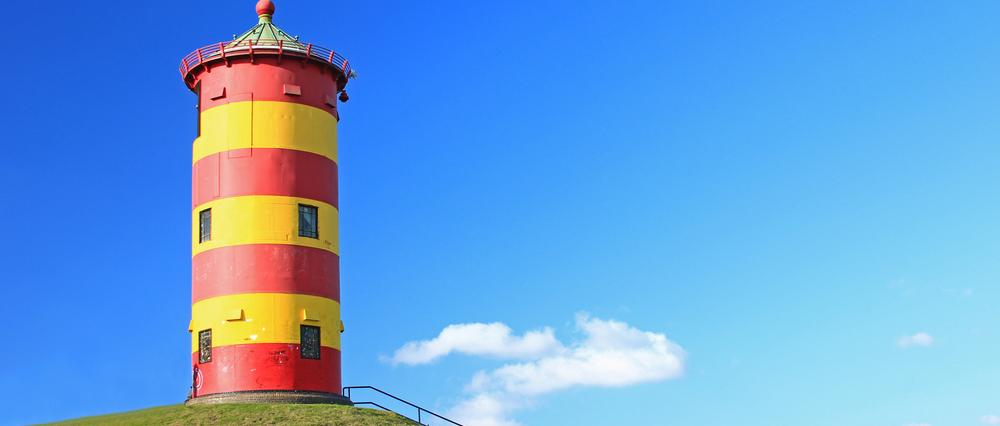 Leuchtturm in rot und gelb auf dem Deich in Niedersachsen