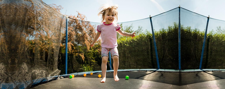 kleines maedchen springt auf trampolin