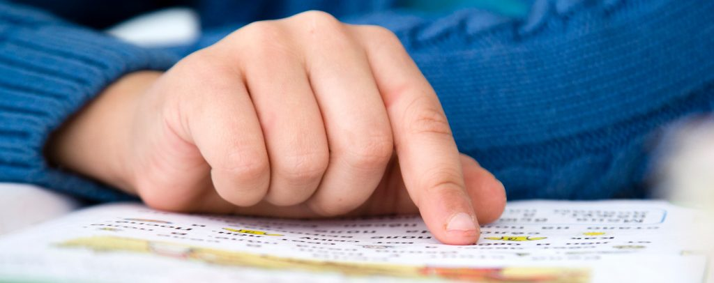 Kind liest mit dem Finger
