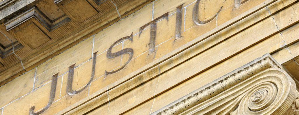 Der Schriftzug Justice prangt an einem alten Gebäude