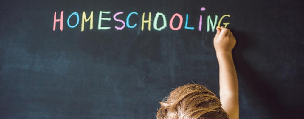 Kind schreibt Homeschooling an die Tafel
