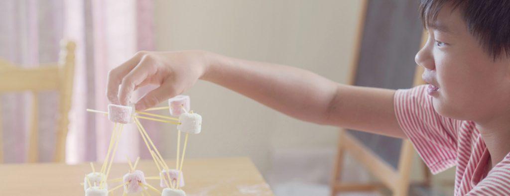 Ein Junge experimentiert mit Styropor und Holzstäbchen