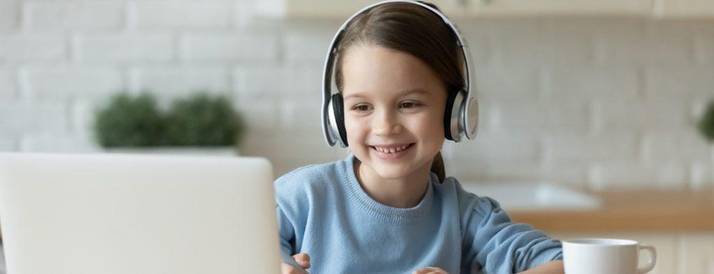 Kind sitzt mit Kopfhoerern am Laptop und lernt mit sofatutor