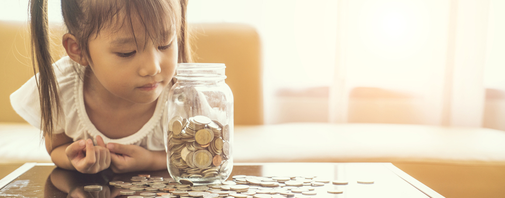Mädchen blickt in ein Glas voller Münzen