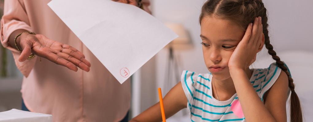 Enttäuschtes Mädchen blickt auf eine schlechte Note