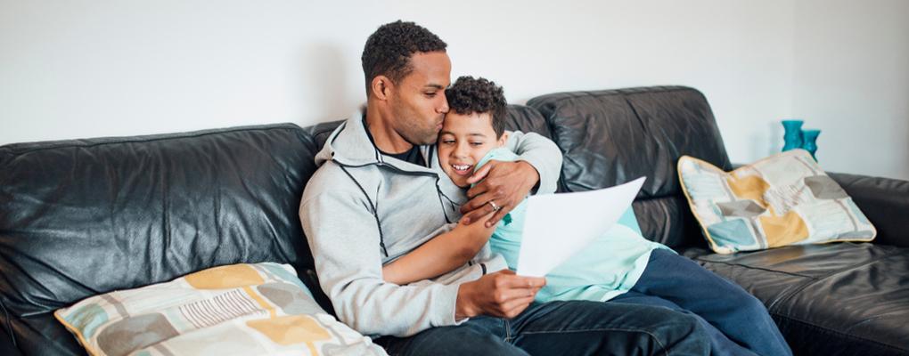 Vater umarmt Sohn und blickt auf ein Schreiben