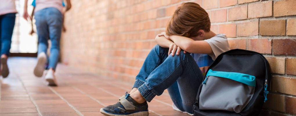 Trauriger Junge sitzt in der Schule alleine auf dem Boden des Flurs