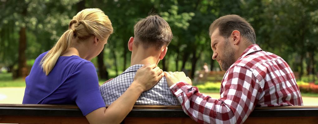 Eltern troesten ihren Sohn und legen ihre Haende auf seine Schultern