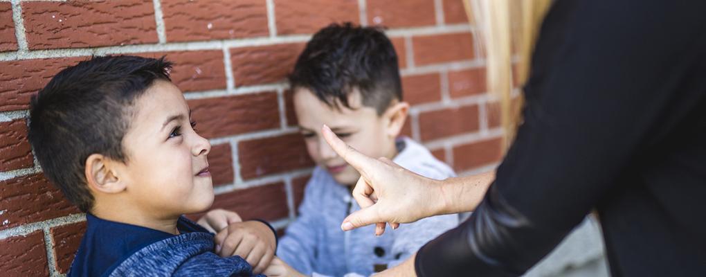 Ein Lehrer ermahnt einen Jungen