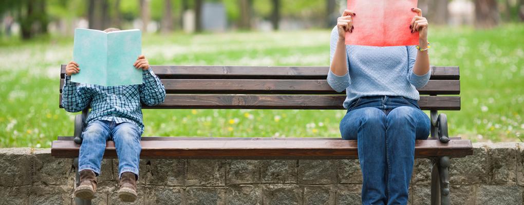 Ein Junge und eine junge Frau lernen auf einer Parkbank