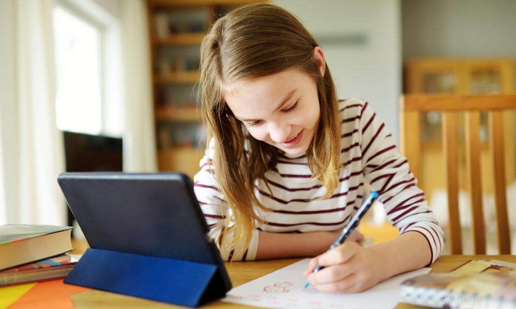 Maedchen lernt mit Tablet am Schreibtisch