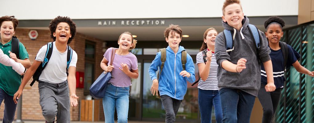Schulkinder rennen außerhalb des Schulgebäudes