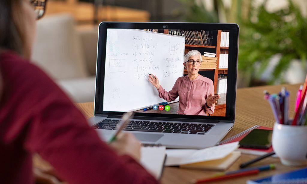 Schülerin sitzt vor einem Tablet, das eine Lehrer beim Unterrichten zeigt