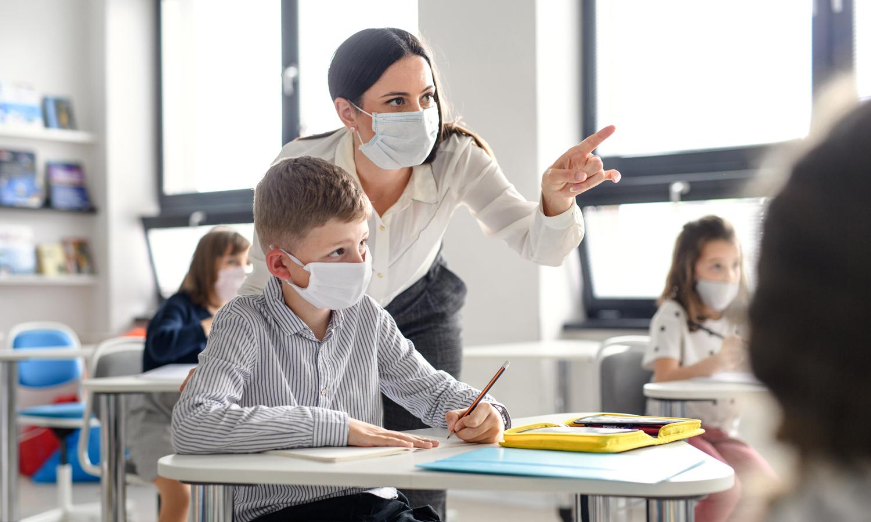 Lehrerin und Schüler mit Maske im Unterricht