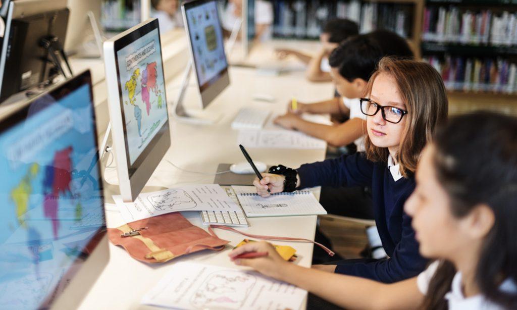 Schülerinnen und Schüler lernen vor einem Computer sitzend