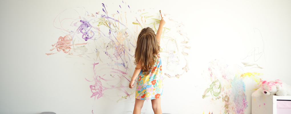 Kind malt eine Wand an