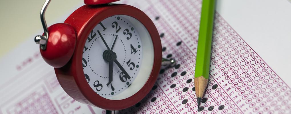 Ein Prüfungsbogen, ein Stift und eine Wecker