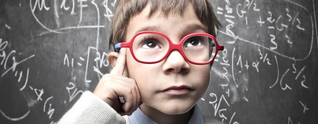 Junge mit Brille steht vor einer Tafel