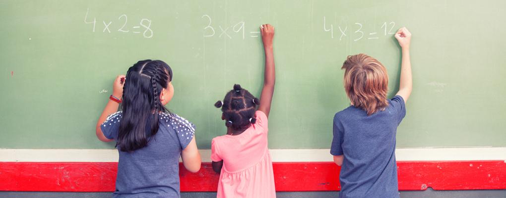 Drei Kinder rechnen an einer Tafel