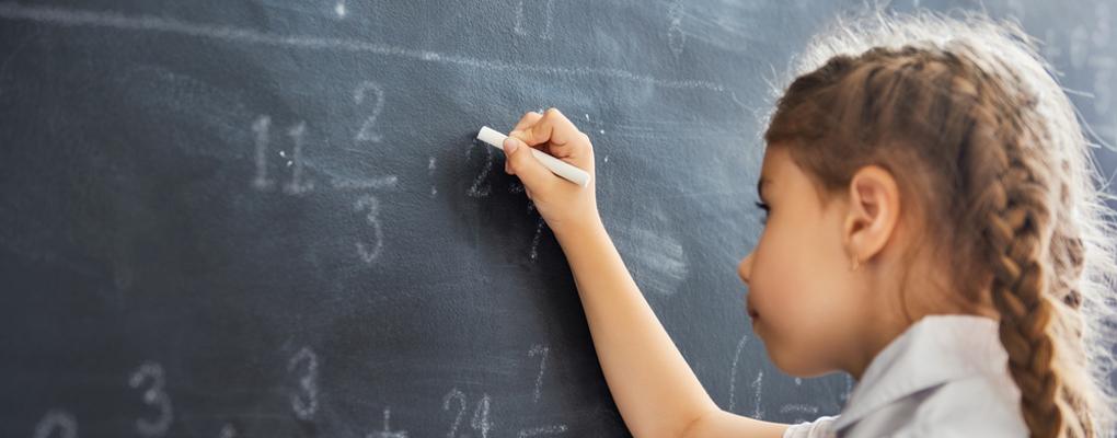 ein Mädchen rechnet an einer Tafel
