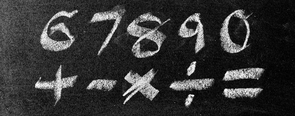 Zahlen und Rechenzeichen stehen auf einer Tafel