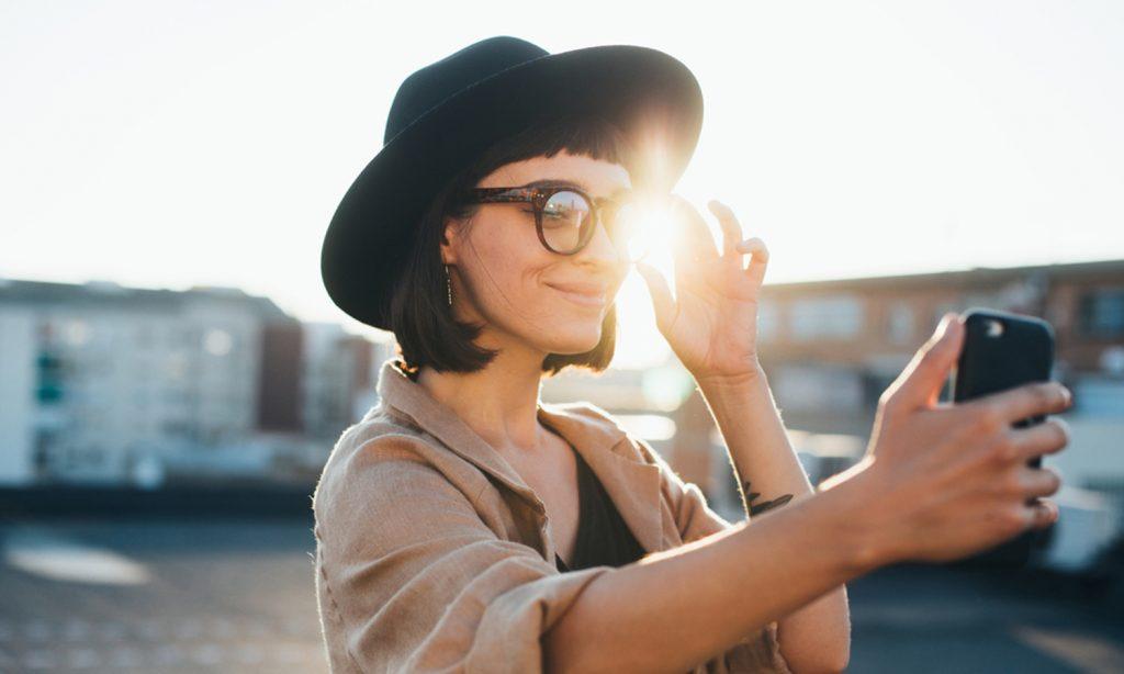 Junge Frau mit Hut hält ein Smartphone in der Hand