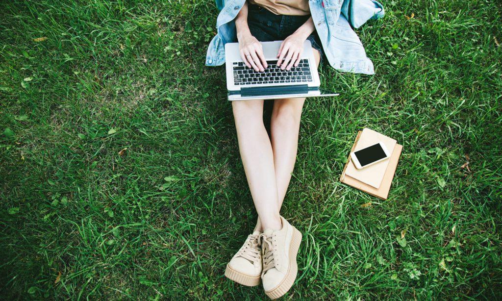 Maedchen sitzt im Gras und lernt mit Laptop auf dem Schoß